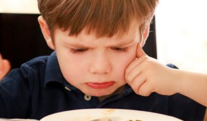 Hungry,child,sitting,in,chair,at,table,in,kitchen,and