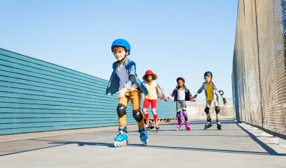 Boy,playing,roller,skates,with,friends,outdoors